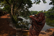 A woman fetches water from a manual water pump against the backdrop of the  Kolaghat thermal power plant in the Shantipur 1 Colonies East Medinipur, India Saturday, Oct. 6, 2012 (Photo/Elizabeth Dalziel for Christian Aid)