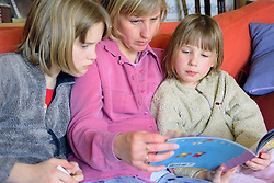 Single mother sitting on sofa reading story book with young daughters,