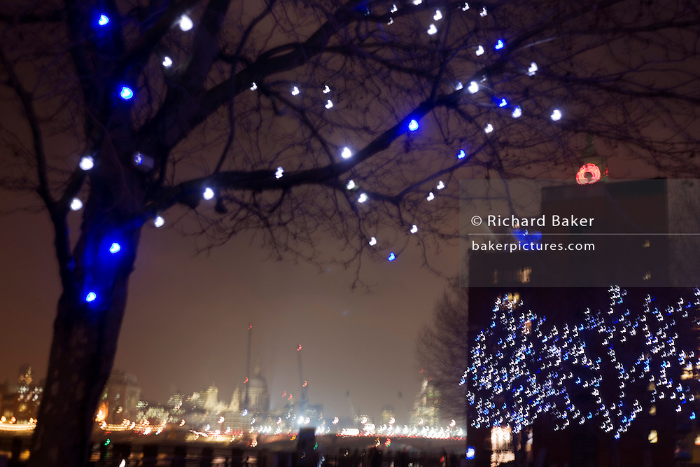 Distant London city lights and decorated trees on South Bank  at night.