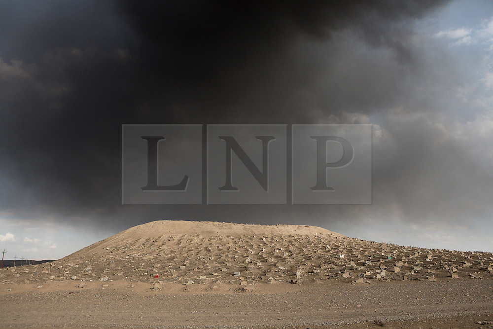 Licensed to London News Pictures. 02/11/2016. Qayyarah, Iraq. Smoke from burning oil wells, set alight by retreating Islamic State militants, clogs the sky over the Qayyarah Cemetery, in the Iraqi town of the same name. Both Shia and Sunni graves within the cemetery were smashed during the town's two year occupation by ISIS extremists who believe that graves should be flat to the earth with no headstone. <br /> <br /> Two months after being liberated from the Islamic State, the Iraqi town of Qayyarah, located around 30km south of Mosul, is still dealing with the environmental repercussions of their ISIS occupation. The town's estimated 15,000 inhabitants constantly live under, and in, heavy clouds of smoke which often envelope the settlement. The clouds emanate from burning oil wells in a nearby oil field that were set alight by retreating ISIS extremists after a two year occupation. The proximity of the fires, often right next to homes within the town, covers many buildings and residents with thick soot and will lead to long term health and environmental implications. Photo credit: Matt Cetti-Roberts/LNP