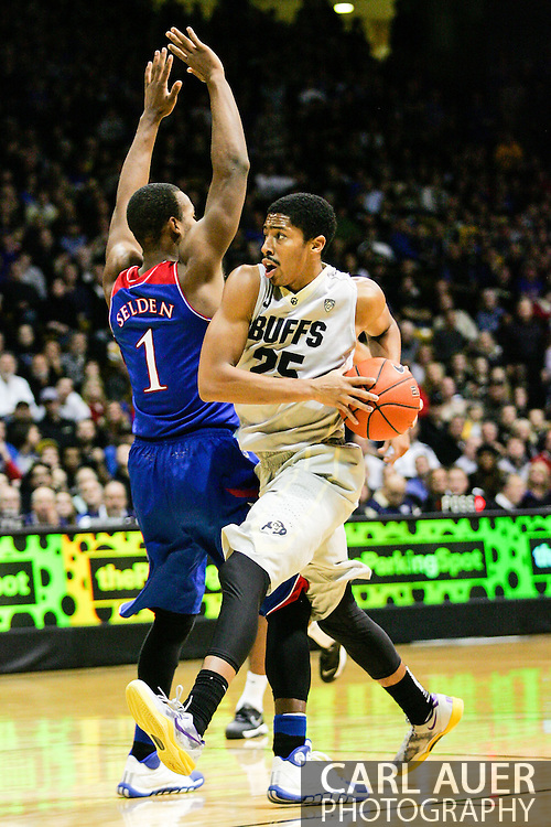 December 7th, 2013:  Colorado Buffaloes junior guard Spencer Dinwiddie (25) makes a move towards the basket past Kansas Jayhawks freshman guard Wayne Selden, Jr. (1) in the second half of the NCAA Basketball game between the Kansas Jayhawks and the University of Colorado Buffaloes at the Coors Events Center in Boulder, Colorado