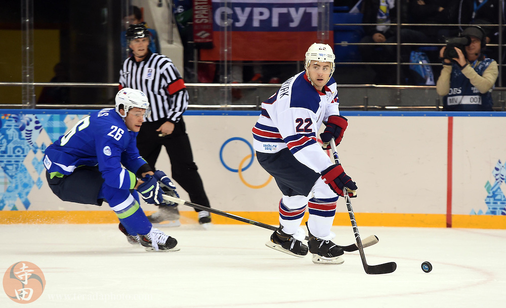 Feb 16, 2014; Sochi, RUSSIA; USA defenseman Kevin Shattenkirk (22) skates with the puck past Slovenia forward Jan Urbas (26) in a men's ice hockey preliminary round game during the Sochi 2014 Olympic Winter Games at Shayba Arena.