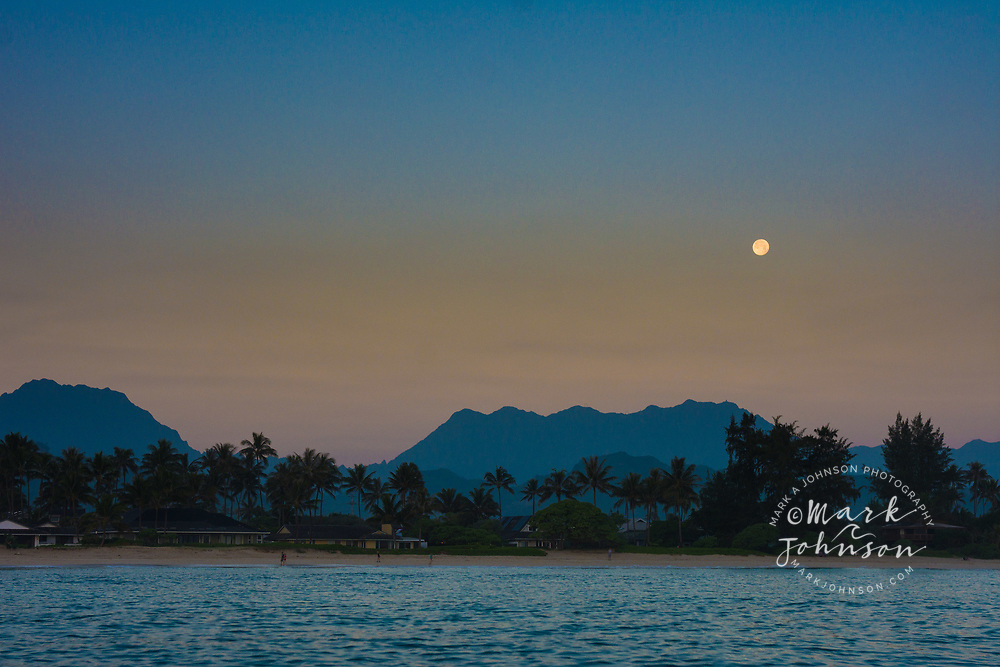 The moon setting over a calm windless morning in Kailua Bay, looking towards the Koolau Mountains, Oahu, Hawaii