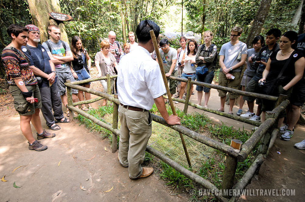 A tour guide demonstrates how one of the many booby traps that were used in the area worked. Inside the fenced area, the grass camouglages a trapdoor that swings down to reveal metal spikes at the bottom of a pit. The Cu Chi tunnels, northwest of Ho Chi Minh City, were part of a much larger underground tunnel network used by the Viet Cong in the Vietnam War. Part of the original tunnel system has been preserved as a tourist attraction where visitors can go down into the narrow tunnels and see exhibits on the defense precautions and daily life of the Vietnamese who lived and fought there.