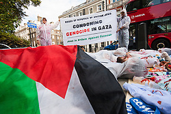 "London, August 4th 2014. Protesters from British Jews Against Genocide lie on the ground surrounded by ""blood"" spattered children's toys and headless dolls symbolising the over 400 children killed in Gaza since Israel's Operation Protective Edge began.continue."