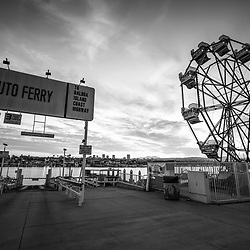 Newport Beach California Balboa Fun Zone high resolution sunrise black and white photo. Includes the Balboa Island Auto Ferry sign, Ferris Wheel, Newport Harbor, and Balboa Island. Newport Beach is a popular coastal city along the Pacific Ocean in Orange County Southern California. Copyright ⓒ 2017 Paul Velgos with All Rights Reserved.
