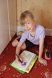 Young girl sitting on floor colouring in picture book using crayons,