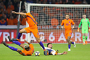 England defender Kyle Walker is tackled on floor and appeals batting with Netherlands Defender Patrick van Aanholt (Crystal Palace) and Netherlands Midfielder Kevin Strootman (Roma), during the Friendly match between Netherlands and England at the Amsterdam Arena, Amsterdam, Netherlands on 23 March 2018. Picture by Phil Duncan.