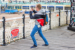© Licensed to London News Pictures. 10/08/2019. Brighton, UK. Members of the public try to stay upright on the Brighton Palace Pier as strong gusts of wind and powerful waves are hitting the seaside resort. Photo credit: Hugo Michiels/LNP