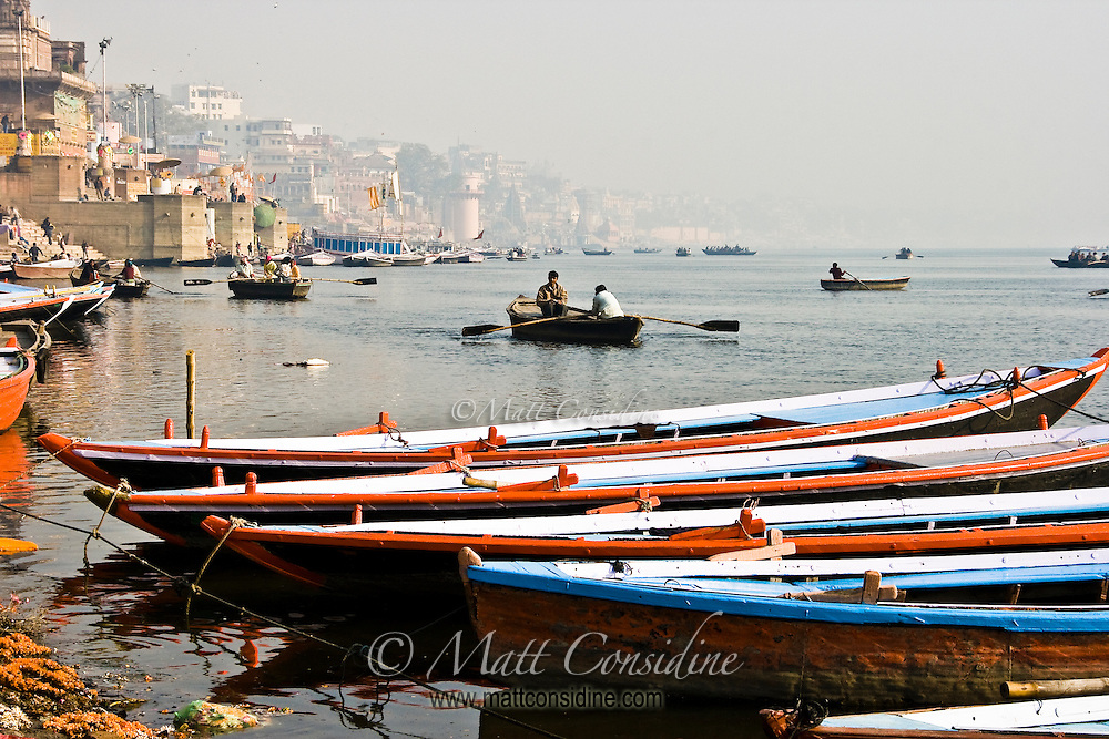 A few boats moored on ghats waiting for tourists while another boatman takes pilgrims on a tour of  Ganges River on a misty morning.<br /> (Photo by Matt Considine - Images of Asia Collection)