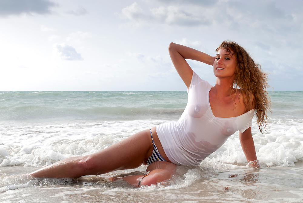 Sensual woman posing in the ocean wet.