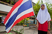 "Sept. 27, 2009 -- PATTANI, THAILAND: A Muslim girl holds the Thai flag before classes at the Gahong School in Pattani, Thailand, Sept 27. Schools and school teachers have been frequent targets of Muslim insurgents in southern Thailand and the army now provides security at many government schools.  Thailand's three southern most provinces; Yala, Pattani and Narathiwat are often called ""restive"" and a decades long Muslim insurgency has gained traction recently. Nearly 4,000 people have been killed since 2004. The three southern provinces are under emergency control and there are more than 60,000 Thai military, police and paramilitary militia forces trying to keep the peace battling insurgents who favor car bombs and assassination.  Photo by Jack Kurtz / ZUMA Press"