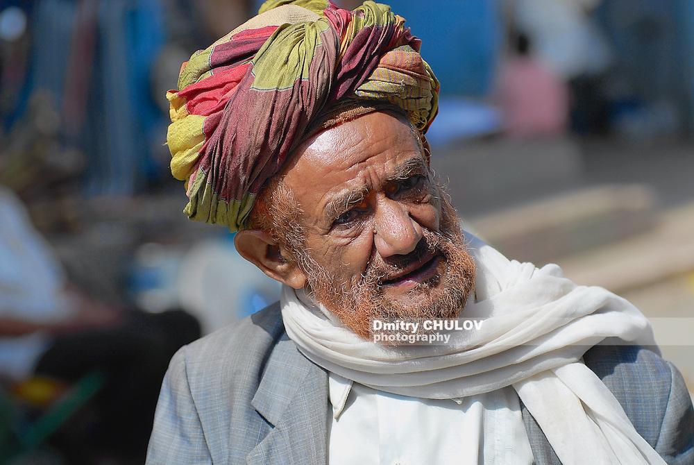 TAIZZ, YEMEN - SEPTEMBER 16, 2006: Portrait of unidentified man in a turban at the street in Taizz, Yemen. Senior men in Yemen cover hair and beard with henna to hide grey hair.
