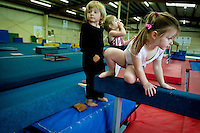 JEROME A. POLLOS/Press..Trinity Reynolds, right, Naomi Steele and Kinzie Thompson, all 3, line up to practice on one of the balance beams Friday at Flip Factory Gymnastics in Coeur d'Alene.
