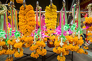 17 OCTOBER 2012 - BANGKOK, THAILAND:   Flower garlands and donations in Wat Mangkon Kamalawat, one of the largest Chinese shrines in Thailand, during the celebration of the Vegetarian Festival. The Vegetarian Festival is celebrated throughout Thailand. It is the Thai version of the The Nine Emperor Gods Festival, a nine-day Taoist celebration celebrated in the 9th lunar month of the Chinese calendar. For nine days, those who are participating in the festival dress all in white and abstain from eating meat, poultry, seafood, and dairy products. Vendors and proprietors of restaurants indicate that vegetarian food is for sale at their establishments by putting a yellow flag out with Thai characters for meatless written on it in red.      PHOTO BY JACK KURTZ