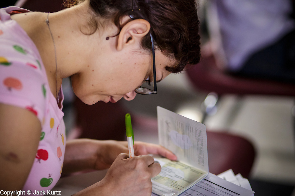 "25 AUGUST 2012 - PHOENIX, AZ: A woman copies information from her passport while she completes the deferred action paperwork Saturday. Hundreds of people lined up at Central High School in Phoenix to complete their paperwork to apply for ""Deferred Action"" status under the Deferred Action for Childhood Arrivals (DACA) program announced by President Obama in June. Volunteers and lawyers specialized in immigration law helped the immigrants complete the required paperwork. Under the program, the children of undocumented immigrants brought to the US before they turned 16 years old would not be subject to deportation if they meet a predetermined set of conditions.     PHOTO BY JACK KURTZ"