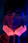 Young woman with glowing pink gloves.Black light
