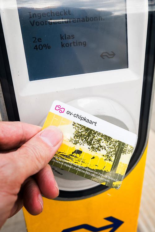Nederland, Driebergen, 4 mei 2015<br /> Inchecken met ov-chipkaart op een paaltje op het perron van een klein station<br /> <br /> Foto: Michiel Wijnbergh