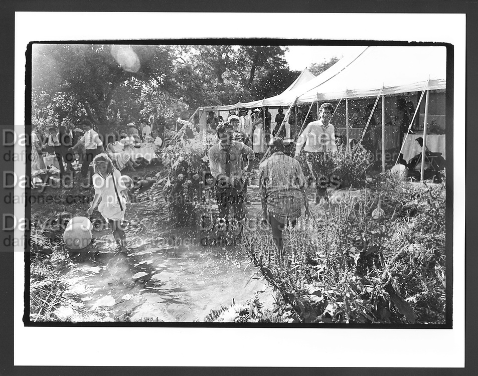 Guests dancing in the pond. Marriage of Ari Campbell- Mcnair-Wilson to<br /> Nick Ashley. Hampshire 1984. This is what happens at a wedding reception by a pond