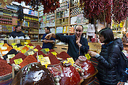 Shopper buying spices in the Misir Carsisi Egyptian Bazaar food and spice market in Istanbul, Republic of Turkey
