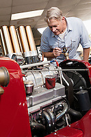 Senior man looking at car engine in automobile repair shop