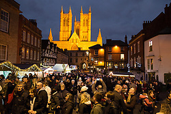 © Licensed to London News Pictures. 3/12/2016. Lincoln, UK. Thousands of people descended upon Lincoln over the weekend to start their Christmas shopping and visit the annual Christmas market. With over 200 stalls surrounding the Cathedral and Castle in the uphill area a one way system to control visitors had to be put in place due to the huge crowds thronging the City Centre. Picture shows the floodlit Cathedral surrounded by Christmas Market stalls and shoppers. Photo credit: Dave Warren/LNP