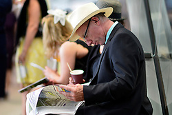 © London News Pictures. 20/06/2013. Ascot, UK. A man reads a copy of the Racing Post. Ladies Day on day three of Royal Ascot at Ascot racecourse in Berkshire, on June 20, 2013. The 5 day showcase event, which is one of the highlights of the racing calendar, has been held at the famous Berkshire course since 1711 and tradition is a hallmark of the meeting. Top hats and tails remain compulsory in parts of the course.  Photo credit : Stephen Simpson/LNP
