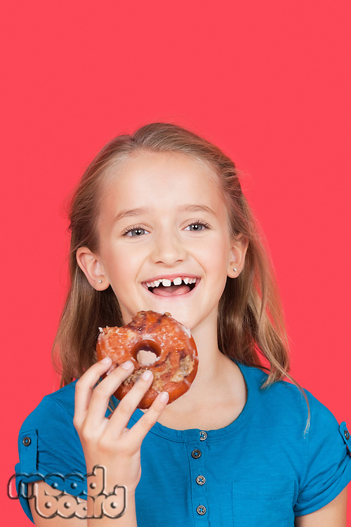 Portrait of happy young girl holding donut against red background