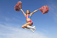 Cheerleader in jumping with pom poms raised mid air