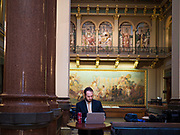 """16 MARCH 2020 - DES MOINES, IOWA: DAN SUNNE, a lobbyist, works by himself in the nearly deserted the State Capitol in Des Moines. Because of numerous reports of Coronavirus in Iowa, the governor is suspending the legislative session for 30 days. It was scheduled to run until mid-April. Sunday night, the Governor announced that the state health department had recorded """"community spread"""" in Des Moines. As a result the State Capitol instituted mitigation measures that included mandatory health screening for everyone going into the building, canceling group tours of the building, and closing the souvenir shop and snack bar.      PHOTO BY JACK KURTZ"""