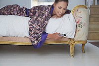 Woman text messaging on bed