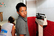 A young boy from the community of Ciudad Romero, having his weight taken as part of a series of medical investigations carried out by the 'Nefrolempa' health team as part of a series of medical investigations carried out by the 'Nefrolempa' health team into the high incidence of chronic renal failure in the region.<br /> <br /> Ciudad Romero, Bajo Lempa, El Salvador. 2011.<br /> The 'Nefrolempa' research project is a collaboration between the El Salvador Ministry of Health, the Nephrology Institute of Cuba's Ministry for Public Health and the United Bajo Lempa Committee Association. The aim of the project is to investigate the reasons for the high levels of Chronic Kidney Disease (CKD) suffered by the communities within the Bajo Lempa region. It is exploring whether the use of agrochemicals might be a factor in the prevalence of the disease.<br /> <br /> Medical team: Dr Elsy Brizuela de Jimenez, Directora Unidad de Salud. Miriam Colindres, Nurse. Maria Eraida Velasquez, clinic and laboratory worker. Ecuilia Castro Peraza, Nutritionist. Veronica Contreras, Education for health. Guadelupe Nunez, Psychologist. Luis Diaz General support worker. Dr Raul Herrera Valdes, Nefrologo, Cuba. Dr Miguel Almaguer Lopez, Nefrologo Cuba. Dr Carlos Orantes, Salvadorean Nefrologist. Dr Juan Carlos Awaya, Salvadorean Nefrologist.