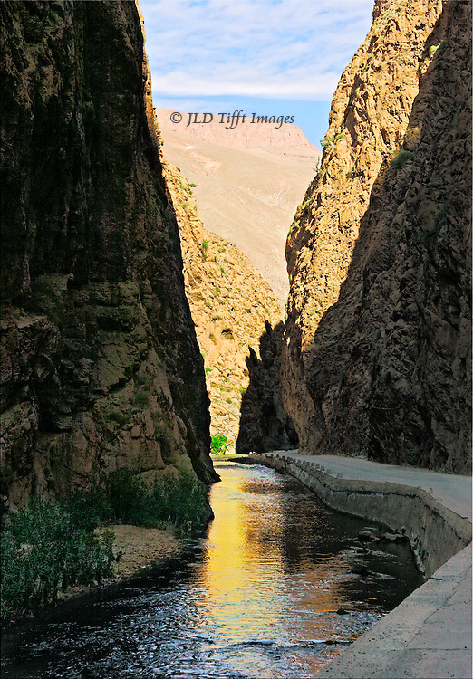View along the diminishing Todra River, through a gorge toward distant mountainous desert.  Landscape of desert, cliffs, and drought-affected river, low in its bed.