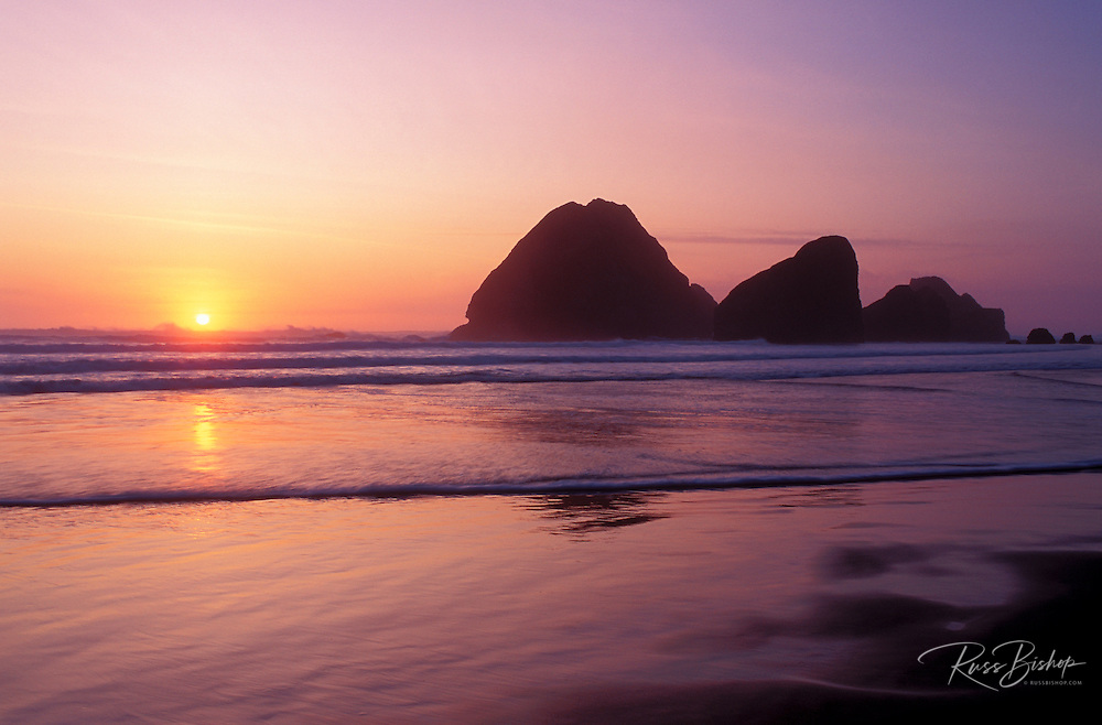 Sea stacks on the beach and sunset over the Pacific Ocean, Pistol River State Park, Oregon.