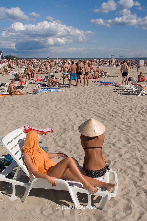 People sunbathing on sandy Pärnu Beach. Young women on foreground. Deck-chair, recliner. Travel Estonia, Europe