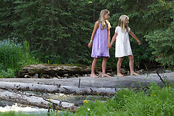 two girls walking on a fallen tree trunk in Montana
