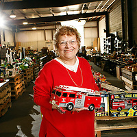 Lesley Bookout holds a fire truck in a warehouse full of toys in Niles. Bookout's husband, Mel, died recently and his family is selling off his massive toy collection where most of the proceeds will go to local charities.<br />