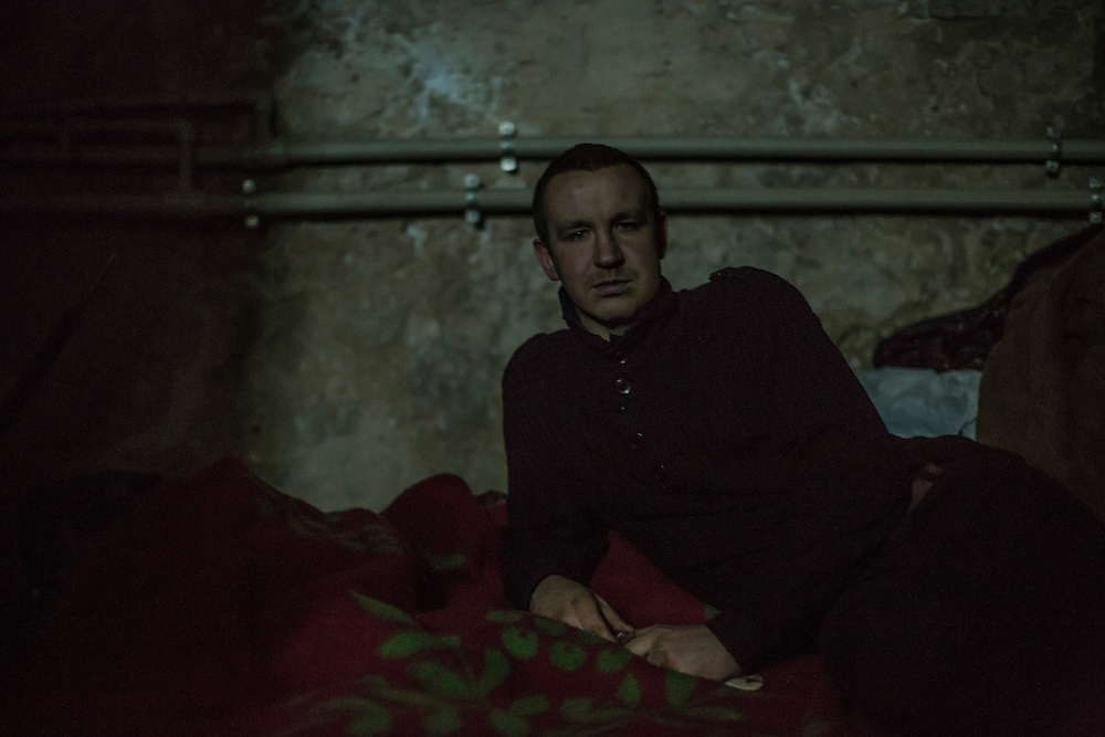 DONETSK, UKRAINE - JANUARY 29, 2015: Yevgeniy Berestovoy, 27, lays on his bed in the dark during a power outage in an underground bomb shelter in the Petrovskyi district of Donetsk, Ukraine. The neighborhood has been shelled heavily in the past few days, forcing many people back to the shelters they first fled to in the summer. CREDIT: Brendan Hoffman for The New York Times