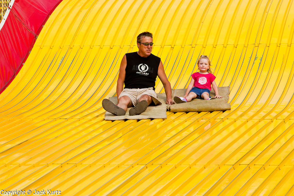 """01 SEPTEMBER 2011 - ST. PAUL, MN:  A father and daughter ride the Giant Slide at the Minnesota State Fair. The Minnesota State Fair is one of the largest state fairs in the United States. It's called """"the Great Minnesota Get Together"""" and includes numerous agricultural exhibits, a vast midway with rides and games, horse shows and rodeos. Nearly two million people a year visit the fair, which is located in St. Paul.   PHOTO BY JACK KURTZ"""