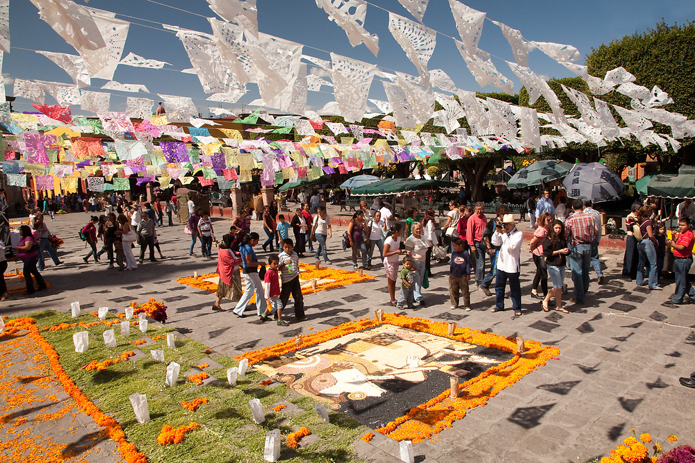 """North America, Mexico, San Miguel de Allende, people under streamers of tissue paper flags, known as """"Papel Picado""""  and elaborate altars of beans and marigolds, in El Jardin plaza during Day of the Dead celebrations."""