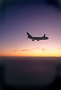 Airplane in flight at sunset