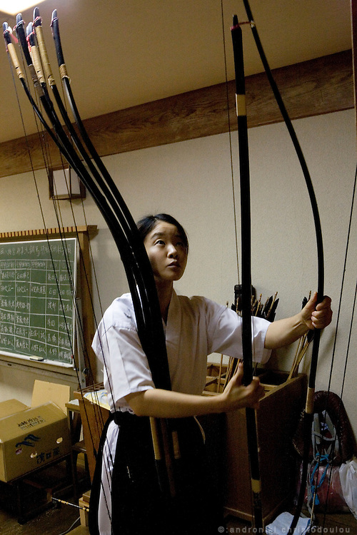 One of the archers taking part in Yabusame (horse-riding archery shinto ritual) aranging the bows in the shrine's dojo (martial arts building), after the morning trainning on the 3rd day of the 3-day anual ritual of Tsurugaoka Hachimangu Shrine in Kamakura