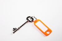 Key with orange key ring tag on white background