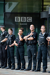 "© Licensed to London News Pictures . 12/07/2014 . Manchester , UK . Police blocking the entrance to the BBC at Quay House as thousands of people protest outside the BBC at Media City in Salford , Greater Manchester , this afternoon (Saturday 12th July 2014) , against Israeli actions in Gaza and the Corporation's coverage of the Israeli Palestinian conflict . A convey branded "" Drive for Justice "" travelled from out of the city from Bradford , Blackburn and other regions , to form the protest . Photo credit : Joel Goodman/LNP"