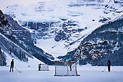 Kids and families play ice hockey on a frozen Lake Louise in winter
