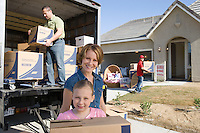 Portrait of family with daughter (7-9) unloading truck