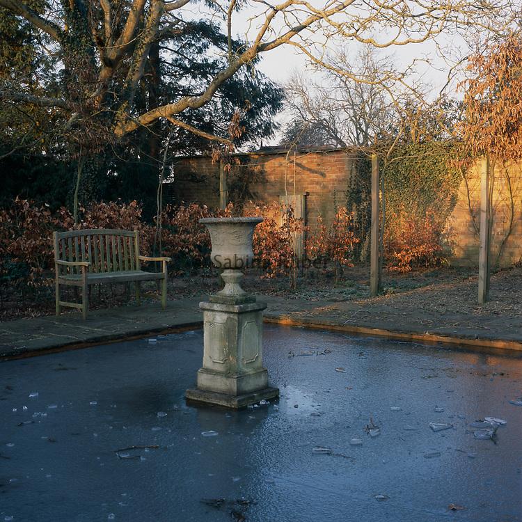 Frozen pond. Bench and Pedestal Urn. Winter: Bryan's Ground, Herefordshire