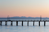 Sunset at the White Rock Pier in White Rock, British Columbia, Canada.  Photographed from White Rock Beach looking west across Boundary Bay towards the mountains on Vancouver Island.