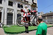 Pessoas tiram fotos de um papai noel de 9 metros de altura, ao lado de uma bicicleta, que é instalado em frente a prefeitura de São Paulo durante a manhã deste sábado. Foto: Nelson Antoine/Frame