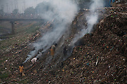 Poor people hunt for anything valuable in a landfill outside a slum settlement in the leather tanning district of Dhaka, Bangladesh.